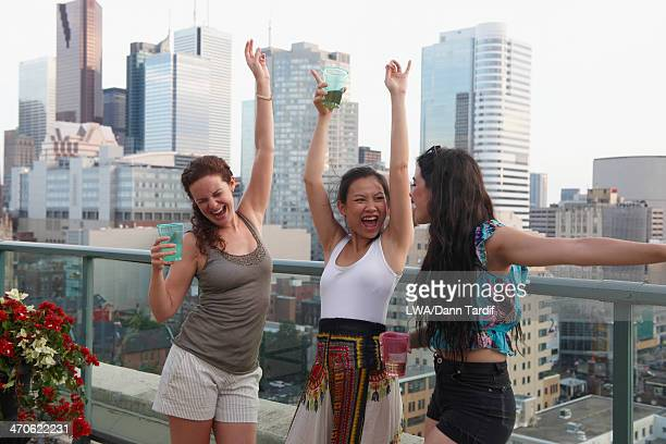 Women enjoying cocktails on urban rooftop