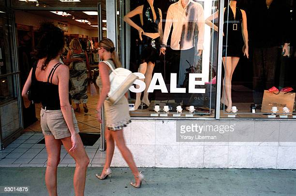 Women enter a clothing store on Colin Street November 10 2003 in Miami Beach Florida In recent years Miami has become an art center for collections...