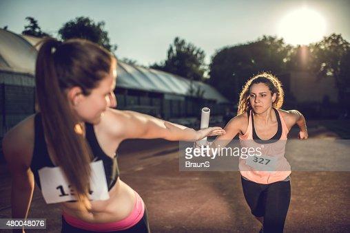女性に対しリレーバトンのスポーツをご堪能ください。