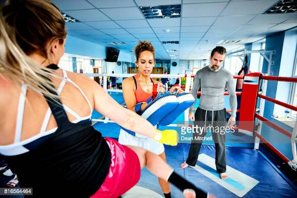Women exercise kicking with their coach