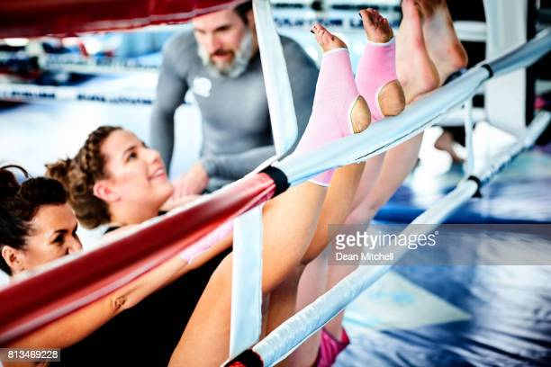 Women exercising in boxing ring with male coach