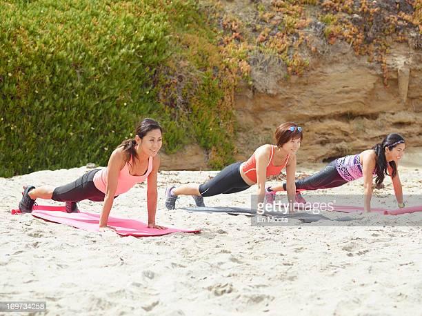 3 women exercising on beach