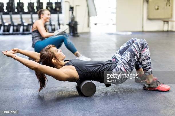 Women exercising on foam rollers in gym