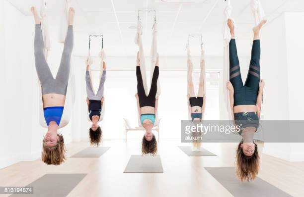 Women exercising upside down during aerial yoga class