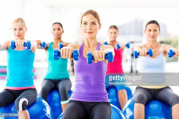 Women Exercising With Weights While Sitting On Exercise Ball