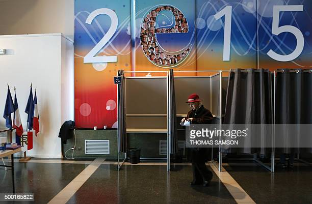 A women exits a polling booth before casting her ballot during the first round of the French regional election at a polling station in Evry on...