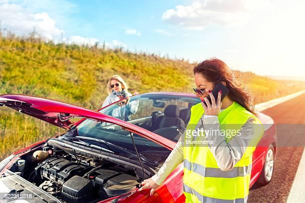 Women experiencing vehicle breakdown on roadside