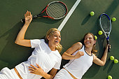 Women Fatigued and Laughing After Tennis Match