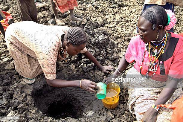Women fetch murky water on March 22 2012 from a hole dug near a dried well in Jamam South Sudan where chronic water shortages for some 35000 refugees...