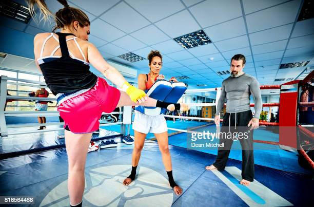Women fighters practicing kickboxing in gym