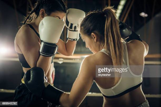 Women fighting on a boxing match in a health club.