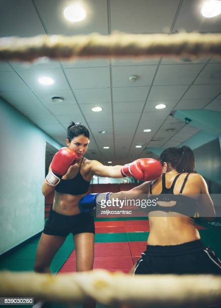 women fighting on a kickboxing training in a ring