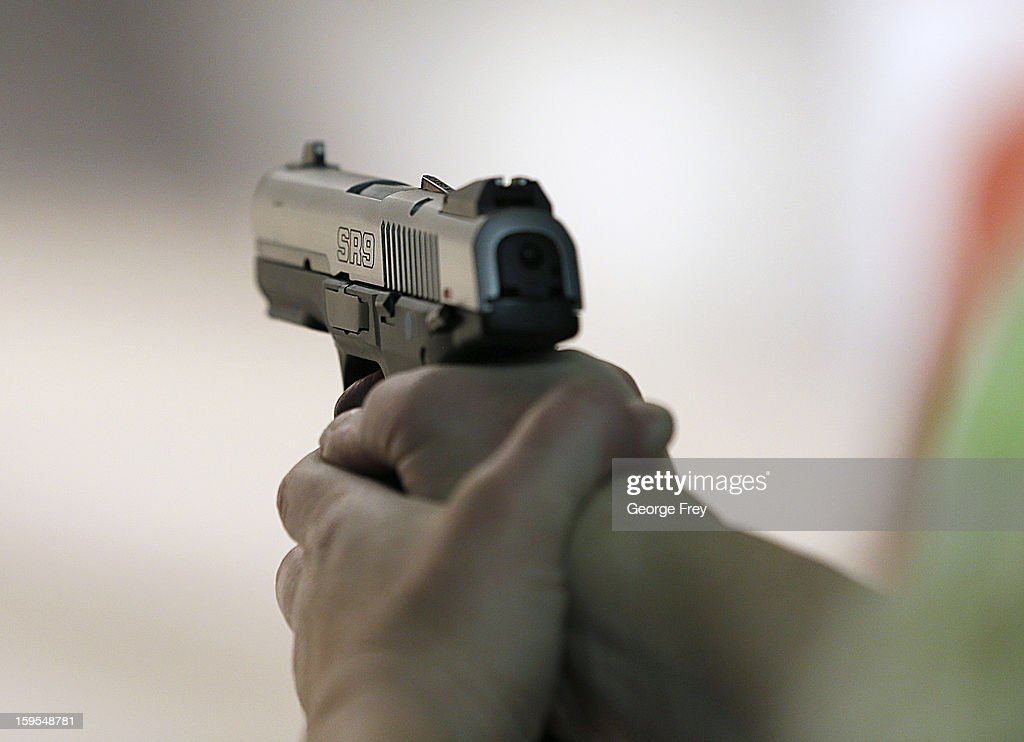 A women fires a handgun at the 'Get Some Guns Ammo' shooting range on January 15 2013 in Salt Lake City Utah Lawmakers are calling for tougher gun...