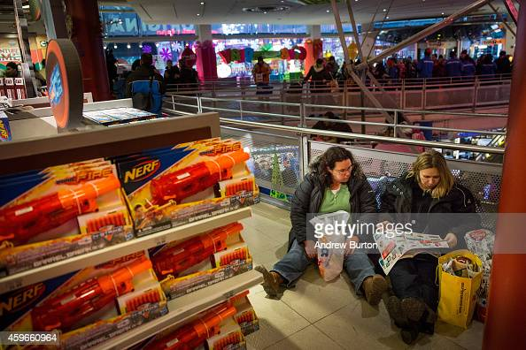 Women flip through a coupon catalog at the Toys R Us in Times Square on November 27 2014 in New York United States Black Friday sales which now begin...