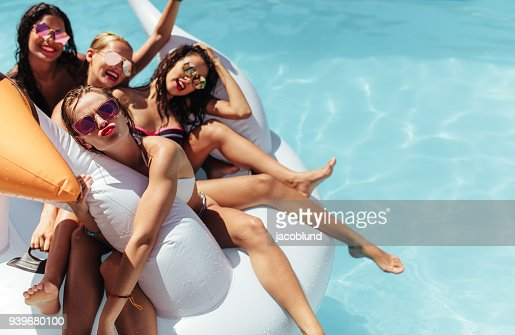 Women floating together on a big inflatable toy in pool : Foto de stock