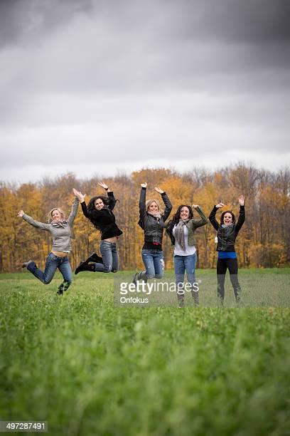 Women Friends Having Fun Jumping in the Air Outdoors