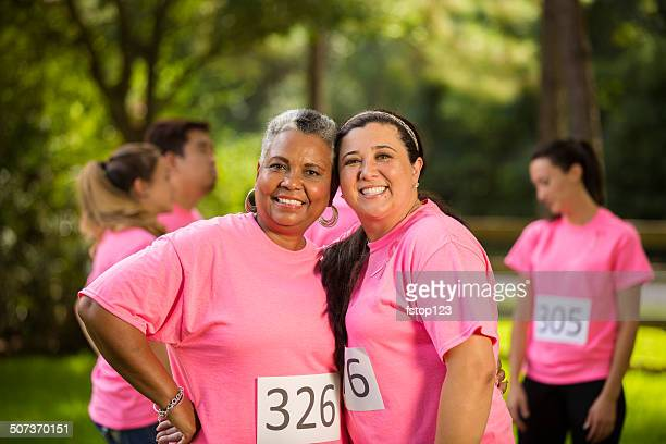Women friends hug after finishing Breast Cancer Awareness charity race.