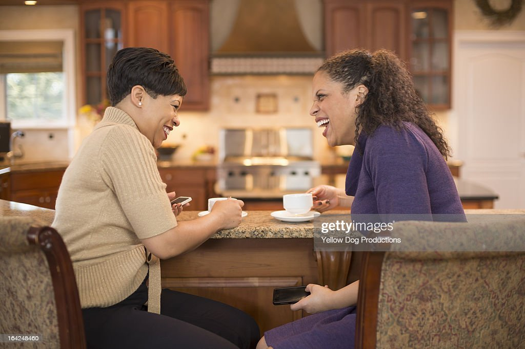 Women Friends laughing and having coffee together : Stock Photo