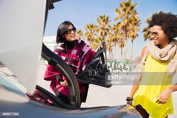 Mujeres amigos de cargar el coche para empezar a un lugar espléndido para las vacaciones