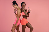 Two female athletes standing with water bottle and smiling after training session. Women friends relaxing after workout.