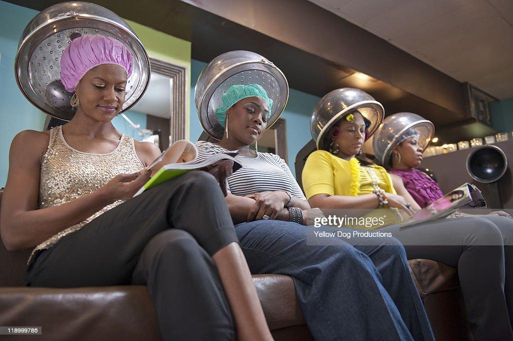 Women friends sitting under hair dryers at salon : Stock Photo