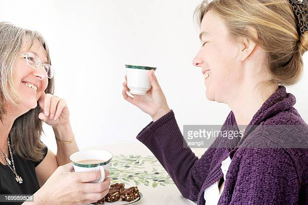 Women friends with hot drink and cake