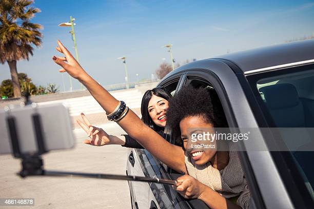Women friends with selfie stick out of the car window