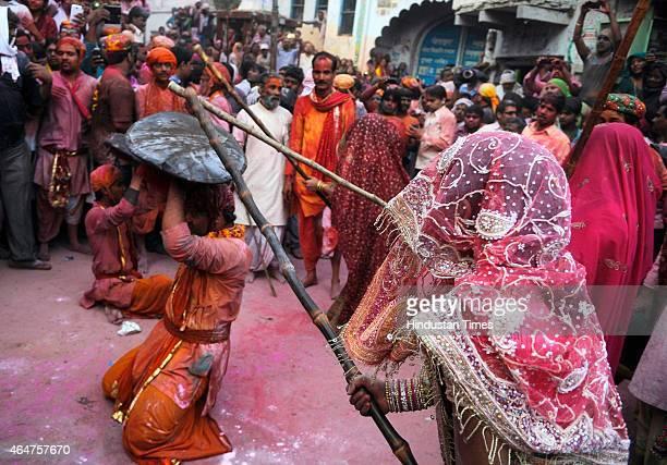 Women from Barsana village beat the shield of men from Nandgaon village with their wooden sticks as they celebrate Lathmar Holi at Barsana Uttar...