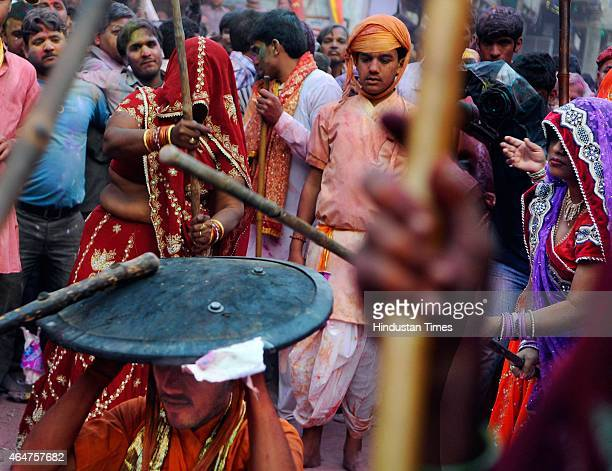 Women from Barsana village beat the shield of men from Nandgaon village with their wooden sticks as they celebrate Lathmar Holi at Barsana Uttar...