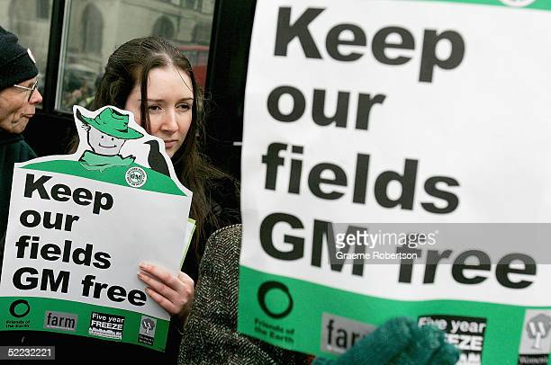 A women from Friends of The Earth holds aloft a placard outside Parliament as part of a demonstration against GM crops February 23 2005 in London...