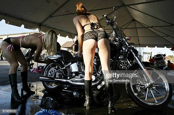 Women from 'Hog Wild Honey's' wear very little while washing Harley Davidson motorcycles during the first weekend of Bike Week March 5 2006 in Ormond...