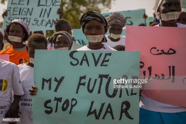 Women from more than forty South Sudanese womens organizations carry placards as march through the city to express the frustration and suffering that...