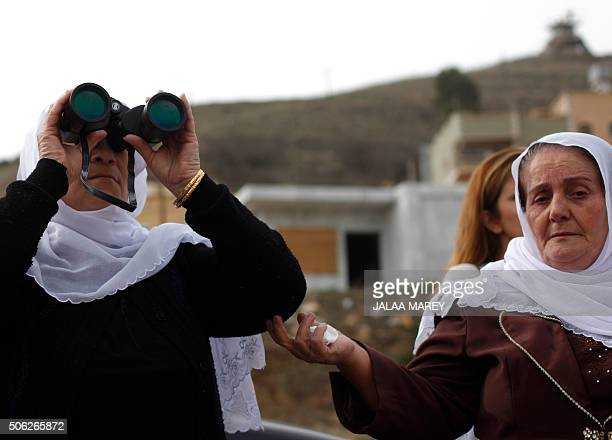 Women from the Druze community in the Israelioccupied Golan Heights use binoculars in the village of Majdal Shams to look towards Loay Marei a Druze...