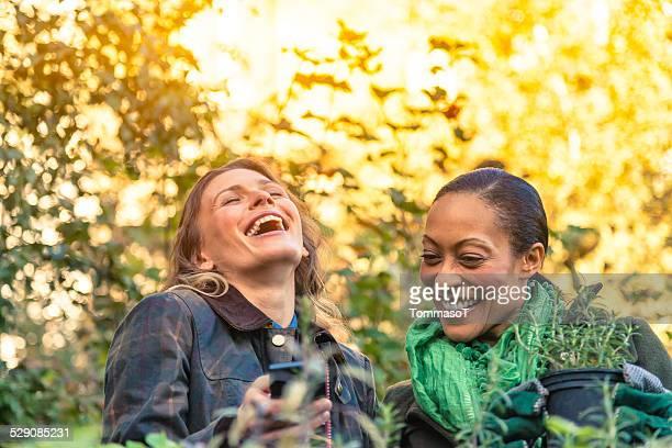 Donne Gardeners ridere guardando uno smartphone