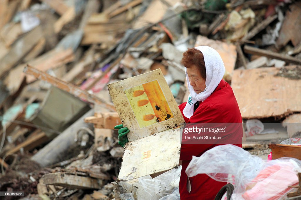 A women gazes at family album found from her destroyed home after an 9.0 magnitude strong earthquake struck on March 11 off the coast of north-eastern Japan, on March 15, 2011 in Noda, Iwate, Japan. The quake struck offshore at 2:46pm local time, triggering a tsunami wave of up to 10 metres which engulfed large parts of north-eastern Japan. The death toll as of Wednesday morning had reached 4,900, with fears that the official death count could well reach up to 10,000 in ''the most tragic event in Japanese history since World War Two''.
