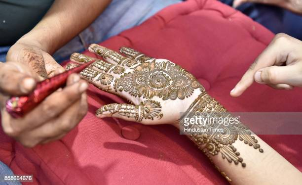 Women gets mehendi done on their hands during the eve of Karva Chauth Festival at Sadar Bazaar on October 7 2017 in Gurgaon India Karva Chauth is a...