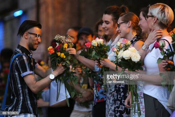 Women give flowers to a member of the muslim community as they attend a vigil outside Finsbury Park Mosque on June 19 2017 in London England...