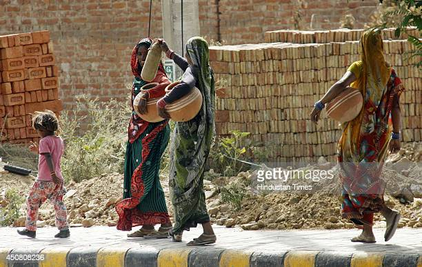 Women going to get drinking water on a hot summer day on June 18 2014 in Gurgaon India Heat wave conditions intensified today in most parts of the...
