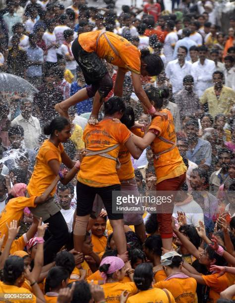 Women Govindas of Girgaumcha Raja Mahila Govinda Pathak build tiers to break the Dahihandi of 10th lane in Kamathipura