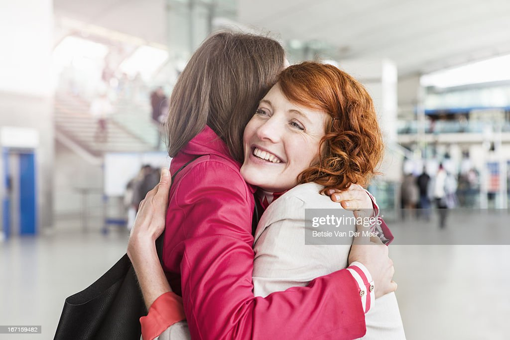 women greeting, embracing, at arrival hall.