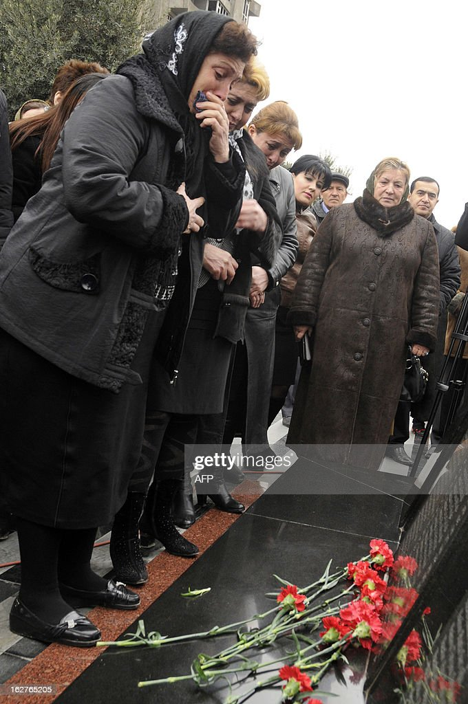 Women grieve at a monument to the victims of what Azerbaijan refers to as the 'Khojaly Massacre' rises in Baku, the capital of Azerbaijan, on February 26, 2013, during a a ceremony to mark 21st anniversary of the tragedy. Azerbaijani authorities say 613 people died when Armenian troops attacked the village of Khojaly in Karabakh in 1992 during Nagorny-Karabakh conflict in what Baku has described as 'genocide', a term fiercely rejected by Yerevan. AFP PHOTO/ TOFIK BABAYEV