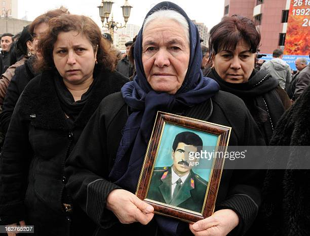 Women grieve at a monument to the victims of what Azerbaijan refers to as the 'Khojaly Massacre' rises in Baku the capital of Azerbaijan on February...