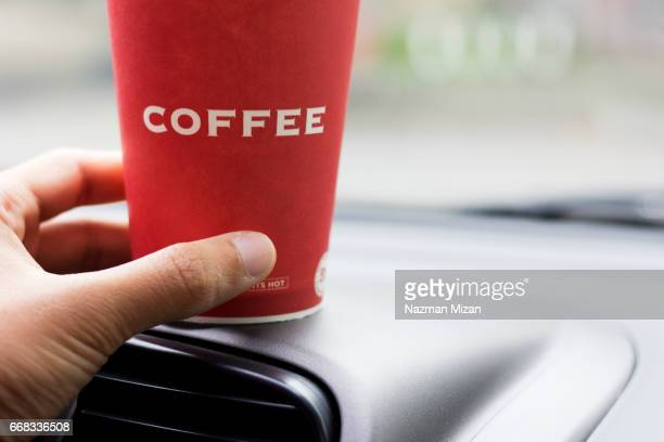 A women hand grabbed a cup of coffee before driving a car.