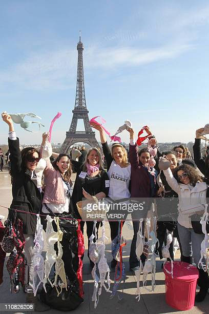 Women hang up bras on the Parvis des droits de l'homme in Paris as they demonstrate on March 20 in Paris during a 'Spring cleaning' event called by...