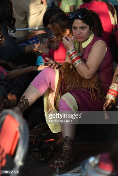 Women have their hands decorated with henna Mehndi on the eve of Karva Chauth at Hanuman Temple Connaught Place on October 7 2017 in New Delhi India...