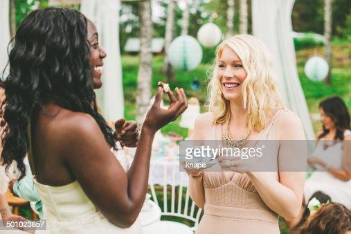 Women having a garden party with dessert table