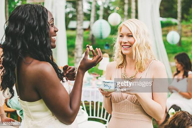 Women having a garden party with dessert table