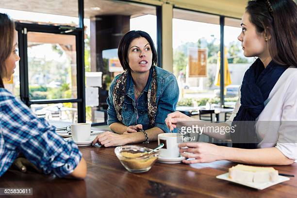 Women Having a Serious Conversation Over a Cup of Coffee