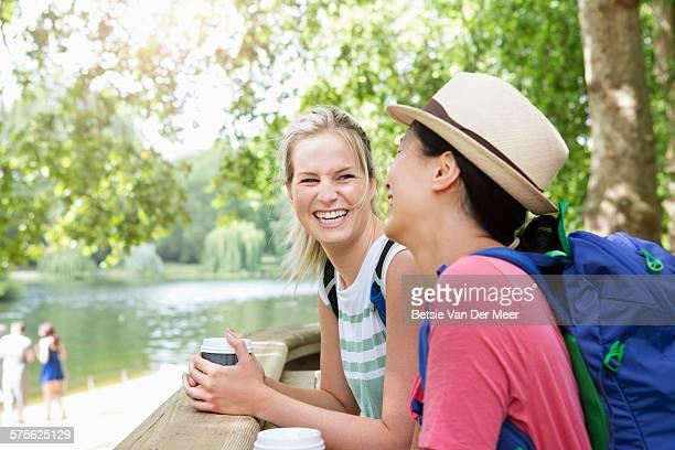 Women having a take-away drink in city park