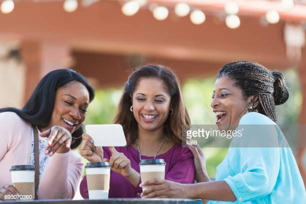 Women having coffee, sharing something amazing on phone